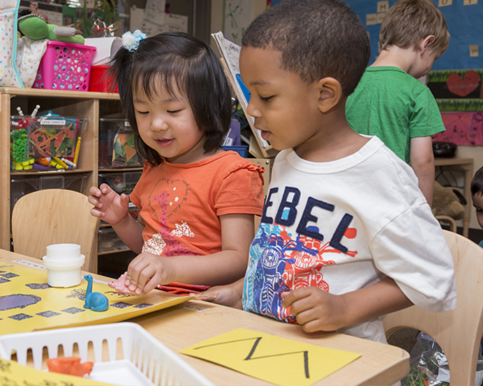 Two young children painting at the Early Learning Center