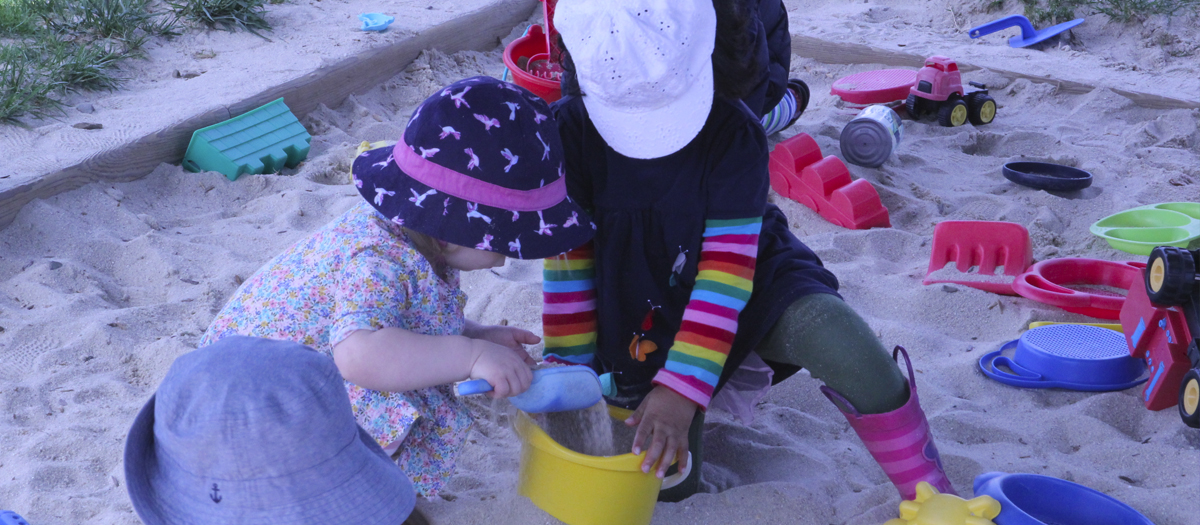 Two students play with pail and shovel in sandbox at the Early Learning Center
