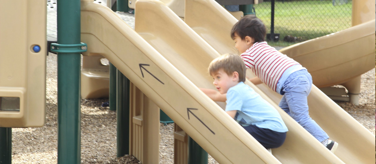 Two children on the slide at the playground in the University of Delaware Early Learning Center